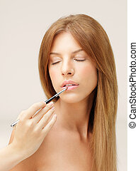 beautiful woman applying lipstick with brush