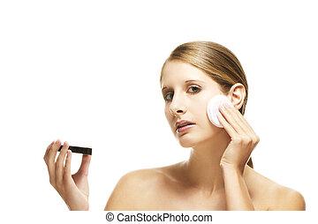 beautiful woman applying makeup on white background