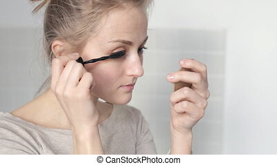 Beautiful woman applying mascara
