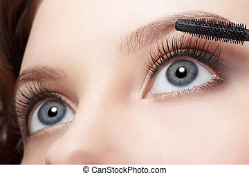 beautiful woman applying mascara - close-up portrait of ...