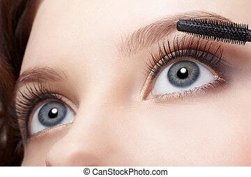 beautiful woman applying mascara - close-up portrait of...