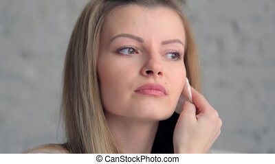 beautiful woman applying skincare lotion to face caring for skin