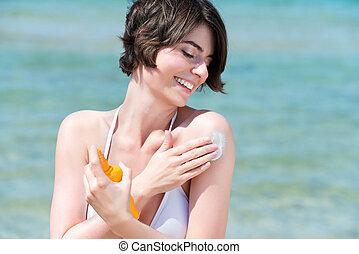 Beautiful woman applying suncream - Beautiful happy young...
