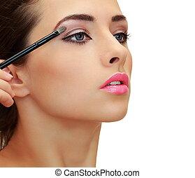 Beautiful woman applying the brush luxury eyeshadows. Closeup isolated profile