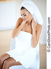 Beautiful woman at a spa with her hair and body wrapped in...