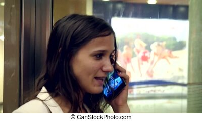 Beautiful woman at cell phone inside an elevator while moving up