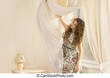 Beautiful woman at the window with curtains