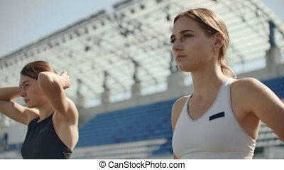 Beautiful woman athlete at the stadium breathing and...