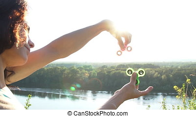 Beautiful woman balancing two fidget spinners on thumbs,...