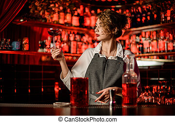 beautiful woman bartender at bar and holds glass of cocktail and looks at it