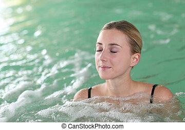 Beautiful woman bathing in spa pool