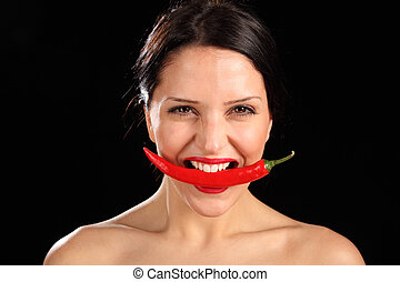 Beautiful woman biting on red chili pepper