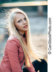 Beautiful woman blond portrait with wind in her hair on sunny day