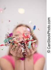 woman blowing confetti in the air