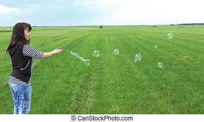 Beautiful Woman Blowing Soap Bubbles on Grass Field