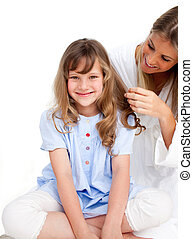 Beautiful woman brushing her daugther\'s hair