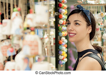 Beautiful woman buying souvenirs in gift shop
