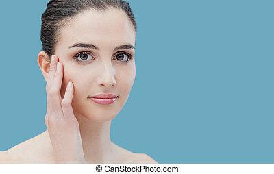 Beautiful woman caressing her face