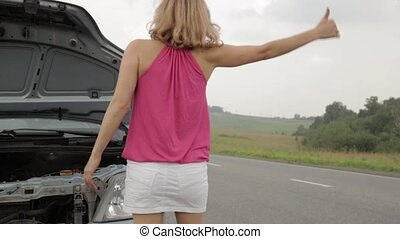 beautiful woman catching a car near a broken car. female driver problems with a car, emergency situation