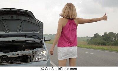 beautiful woman catching a car near a broken car. female...