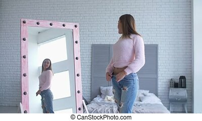 Beautiful woman checking her body shape in mirror