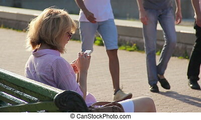 """Beautiful woman checking newsfeed in social network on smartphone, using gadget"""