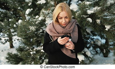 Beautiful woman checks messages near pines covered with snow.