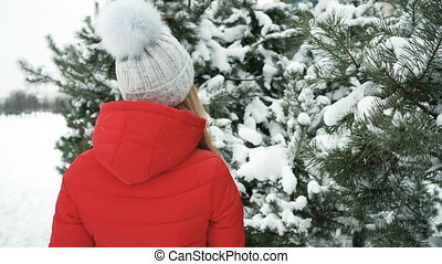 Beautiful woman cheerfully walks at coniferous trees covered by snow