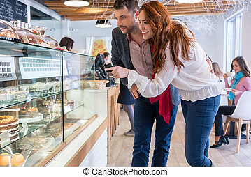 Beautiful woman choosing a delicious cake while standing next to her boyfriend