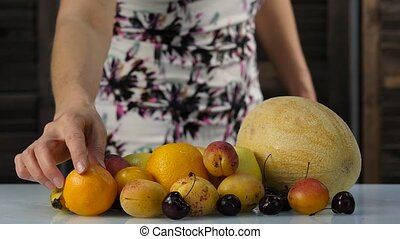 Beautiful woman choosing fruits. Healthy eating. Weight loss and dieting concept. slow motion