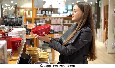beautiful woman choosing utensil dishes in a store...