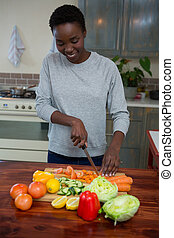 Beautiful woman chopping vegetables in kitchen