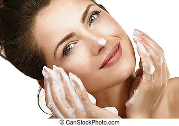 Beautiful woman cleaning her face with a foam treatment on white