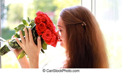 Beautiful woman closeup smiling and sniffing aroma of...