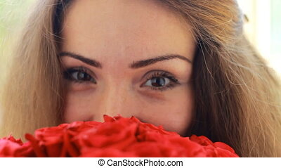 Beautiful woman closeup with a bouquet of flowers of red roses.