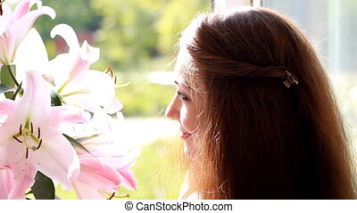 Beautiful woman closeup with flower lily. Advertisement....