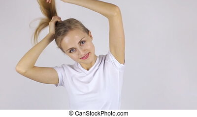 Beautiful woman collects her hair in a ponytail - Beautiful...