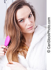 Beautiful woman combing hair