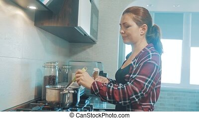 Beautiful woman cooking and testing food in kitchen. girl indoors pours grated pepper soup prepares food. prevents the water the pot. mother cook concept lifestyle