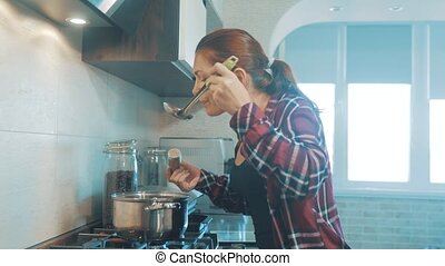 Beautiful woman cooking and testing the food in the kitchen....