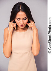 Beautiful woman covering her ears with fingers