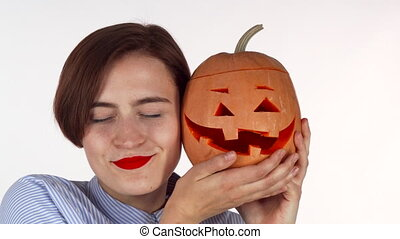 Beautiful woman cuddling with Halloween carved Jack pumpkin