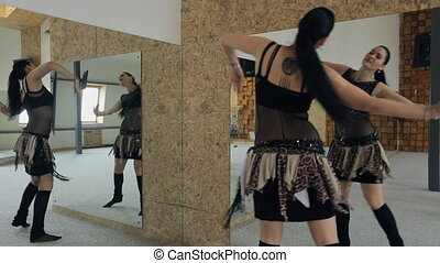 Beautiful woman dances belly dance in studio with many mirrors. View from back.