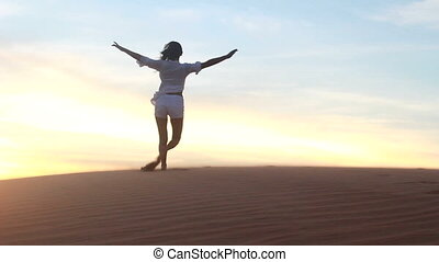 Beautiful woman dancing in desert