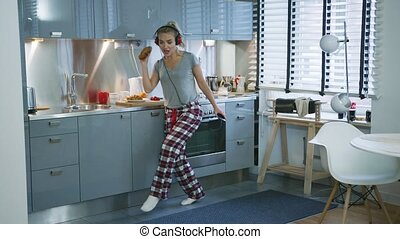 Beautiful woman dancing in kitchen - Attractive young woman...