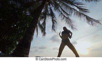 Beautiful woman dancing on the beach
