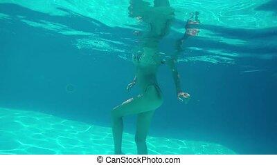 Beautiful woman dancing undewater in pool