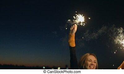 Beautiful woman dancing while holding sparkler. Beautiful...