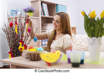Beautiful woman decorating home for easter