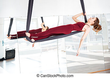 Beautiful woman doing antigravity yoga in studio